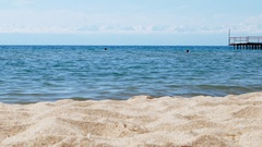People in the Lake Issyk-Kul in the background of mountains, beach town of Stock Footage