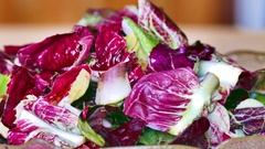 Fresh mixed green salad in bowl on wooden table close up - zoom out Stock Footage