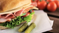 Sub sandwich with fresh vegetables, lunch meat and cheese on hoagie roll. Stock Footage