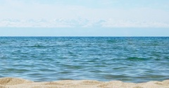 Waters of the lake Issyk-Kul in the background of mountains, beach town of Stock Footage