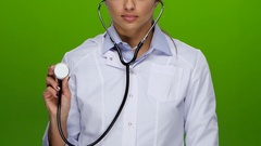 Doctor girl listening to stethoscope, dressed in white medical gown and shirt Stock Footage