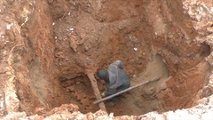 Excavator digs a hole for the connecting pipeline Stock Footage