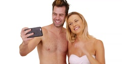 Happy millennial couple taking pictures with smartphone at the beach Stock Footage