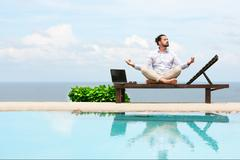 Businessman wearing a suit doing Yoga on the beach Stock Photos