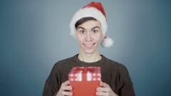 Young man in Santa hat opening a gift box with a surprise inside seeing Fuck You Stock Footage
