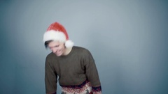 Man in Santa hat opening gift box unexpectedly hand from a box grabs him by nose Stock Footage