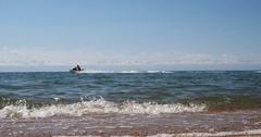 On the hydrocycle on Lake Issyk-Kul in the background of mountains, beach town Stock Footage
