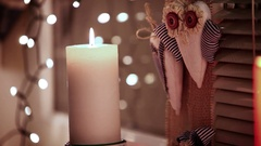Warm-toned Christmas footage: candle and handmade decorations on the window Stock Footage