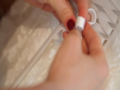 Best friend helps future bride to wear a wedding dress. closeup. Stock Footage