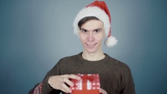 Man in Santa hat opening gift box unexpectedly hand from a box clicks it on nose Stock Footage
