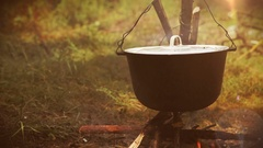 Campfire scene: a pot with food hangs over the fire Stock Footage