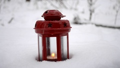 Red candle lantern with candle in snow during snowfall Stock Footage