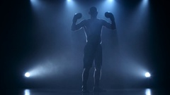 Strong and muscular body of a boxer in silhouette Stock Footage