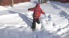 Boy sneaks on snowdrift Stock Footage