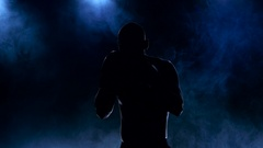 Silhouette of boxer who trains strike blows Stock Footage