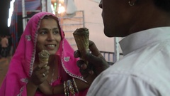 Indian couple eating ice cream in traditional dresses at the Pushkar Mela, a car Stock Footage