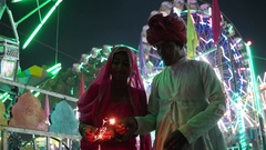 Indian couple in traditional dress with fire sparkle cracker at Diwali Mela fest Stock Footage