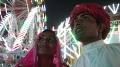Indian traditional couple talking in pink sari and red turban at Pushkar Mela, a Stock Footage