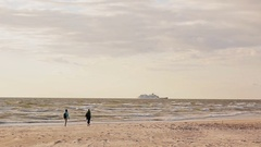 In a distance two women with backpacks are walking barefoot on a sandy beach Stock Footage
