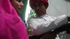Indian traditional couple firing air pistol gun at balloons at Pushkar Mela, a c Stock Footage