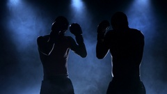 Sparring of two boxers in the studio. Silhouette, smoke Stock Footage