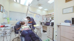 Patient at procedure: dental therapist and his assistant are drilling tooth. Stock Footage