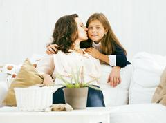 Happy smiling mother with little cute daughter at home interior Stock Photos