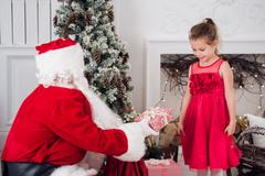 Santa Claus and children opening presents at fireplace. Kids father in costume Stock Photos