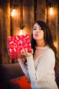 Attractive sensual young female with gift box sending a kiss over glittering Stock Photos