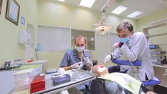 Dental therapist, his assistant and lady as patient at stomatological procedure Stock Footage