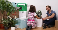 Young Mixed Race Family Unpacking a Plant Fragile Product Moving Home Apartment Stock Footage
