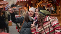 Three Girlfriends Taking a Selfie with Smart Phone on the Christmas Market Stock Footage