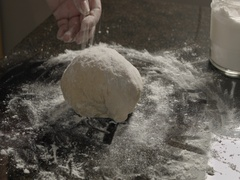Elderly woman kneads dough on the table Stock Footage