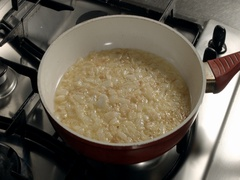 Chopped onion is fried in oil in a frying pan and moved by a wooden spatula Stock Footage