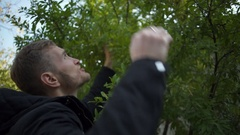 Young handsome man picking an apple from a tree slow motion Stock Footage