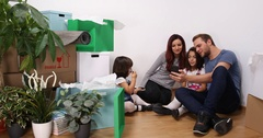Happy Young Family and Kids Talk Video Call Mobile Phone Show Keys New Home Room Stock Footage
