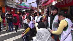 Asiatics are performing a massage with knifes in the Dihua Street, Taiwan. 4K Stock Footage