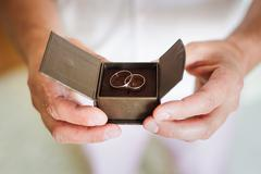Groom holding a beautiful box with wedding rings Stock Photos