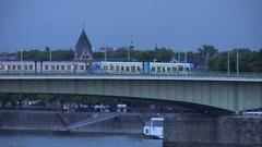 4K Pan right tramway traffic cross bridge in Koln at twilight follow tram train Stock Footage