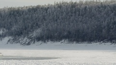 Lonely ship or boat staying on river covered with ice in winter at background of Stock Footage
