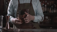 Bartender is making cocktail at bar counter, adding some bitter in the shaker Stock Footage