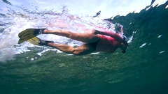 Snorkeling - woman swims rapidly over coral reef, Red sea, Dahab, Sinai Stock Footage
