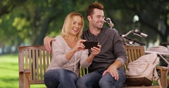 Millennial couple watching videos on smartphone together in the park Stock Footage