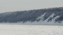Tugboat stucked on river covered with ice in winter at background of snow forest Stock Footage