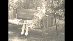Vintage 16mm film, 1940 Americana, people on outdoor bench swing Stock Footage