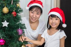 Asian Chinese mother and daughter decorating Christmas tree at home Stock Photos