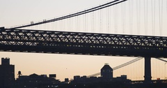 Silhouette of a subway train passing over the Williamsburg Bridge at sunset - 4k Stock Footage