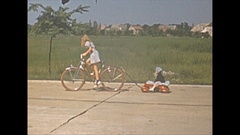 Vintage 16mm film 1940 Americana, girl on bike pulling little brother in wagon Stock Footage
