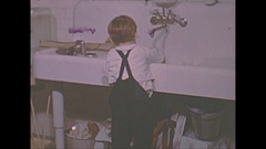 Vintage 16mm film, 1940 Americana, child at sink. trying to clean dishes Stock Footage