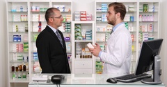 Experienced Pharmacist Discussing with Patient About Drug Medication in Pharmacy Stock Footage